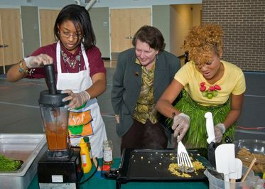 2 black women doing cooking demonstration with onlooker